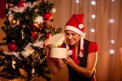 Frau nahe dem Weihnachtsbaum, der inneres Geschenk schaut Lizenzfreie Stockbilder