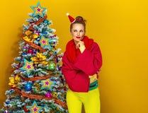 Frau nahe dem Weihnachtsbaum lokalisiert auf gelbem Hintergrund Lizenzfreie Stockbilder