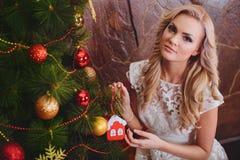 Frau nahe einem neu-jährigen Baum mit Geschenken Stockfoto