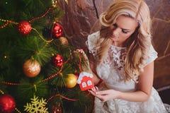 Frau nahe einem neu-jährigen Baum mit Geschenken Lizenzfreie Stockfotos
