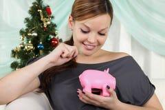 Frau nahe einem Weihnachtsbaum denkt an ihre Sparungen Lizenzfreies Stockbild