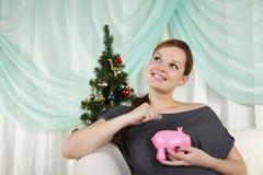 Frau nahe einem Weihnachtsbaum denkt an ihre Sparungen Stockfoto