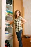 Frau nahe Garderobe mit Bettwäsche Stockbilder