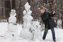Frau nahe Schneemännern Stockfotos