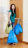 Frau nahe Tür mit Abfalltaschen lizenzfreie stockbilder