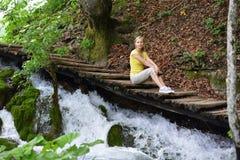 Frau nahe Wasserfällen Stockbild