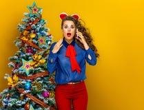 Frau nahe Weihnachtsbaum auf gelbem Hintergrund unter Verwendung des Handys Lizenzfreies Stockbild