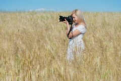 Frau nehmen ein Foto mit Kamera auf einem Gebiet Stockfoto