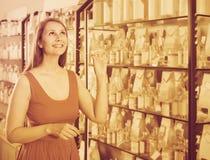 Frau nehmen einem choise frisches Parfüm im Parfümsupermarkt Lizenzfreie Stockfotos