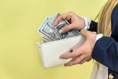 Frau nimmt Dollar von der Geldbörse heraus Stockfotografie