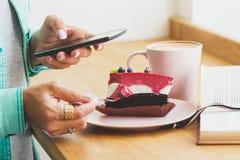 Frau nimmt ein Bild der Schale mit Cappuccino und ein Stück des Nachtischs auf der Platte Lizenzfreie Stockfotos