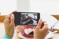 Frau nimmt ein Bild der Schale mit Cappuccino und ein Stück des Nachtischs auf der Platte Lizenzfreie Stockfotografie
