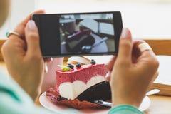 Frau nimmt ein Bild der Schale mit Cappuccino und ein Stück des Nachtischs auf der Platte Stockfotografie