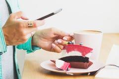 Frau nimmt ein Bild der Schale mit Cappuccino und ein Stück des Nachtischs auf der Platte Stockbild