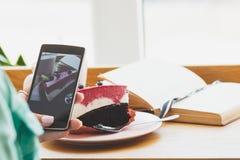 Frau nimmt ein Bild der Schale mit Cappuccino und ein Stück dess Lizenzfreies Stockbild