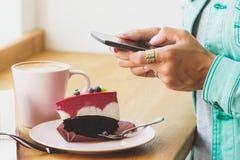 Frau nimmt ein Bild der Schale mit Cappuccino und ein Stück dess Stockfotos