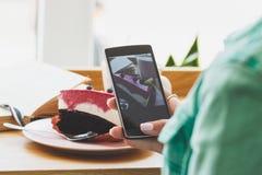 Frau nimmt ein Bild der Schale mit Cappuccino und ein Stück dess Stockfotografie