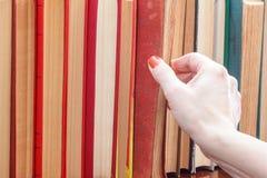 Frau nimmt ein Buch von einem Bücherregal Viele Bücher des gebundenen Buches an Stockfotografie