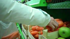 Frau nimmt eine Karotte vom Regal im Markt, hd Video stock footage