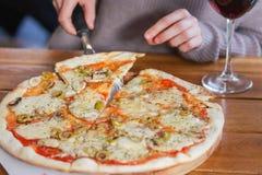 Frau nimmt eine Scheibe der geschnittenen Pizza mit Mozzarellakäse, Tomaten, Pfeffer, Olive, Gewürzen und frischem Basilikum Ital lizenzfreie stockbilder