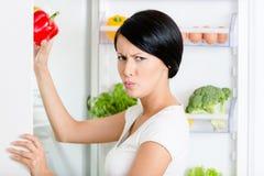 Frau nimmt grünen Pfeffer von geöffnetem Kühlschrank Stockfotos
