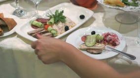Frau nimmt Platte des Lebensmittels und setzt sich auf dem Tisch stock footage