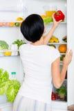 Frau nimmt roten Pfeffer von geöffnetem Kühlschrank Stockfotos