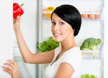 Frau nimmt süßen Pfeffer von geöffnetem Kühlraum Stockbilder
