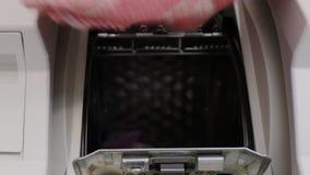 Frau nimmt Wäscherei aus Waschmaschine heraus stock video