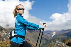 Frau Nordic, der in den Bergen geht und trainiert Lizenzfreies Stockfoto