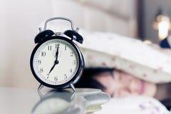 Frau oben aufgeweckt durch die Geräusche der Alarmuhr Stockbild