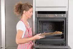 Frau am Ofen lizenzfreies stockbild