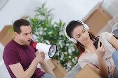 Frau online während verärgerter Mann, der durch Megaphon nennt Lizenzfreie Stockfotografie