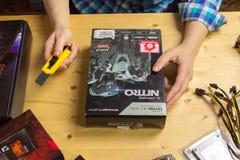 Frau packt mit Teppichmesser eine neue Videokarte zu Ihrer Co aus Stockbild