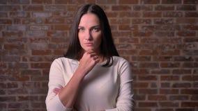 Frau passt durchdacht zur Kamera mit ihrem Arm nahe dem Kinn auf auf, Hintergrund bricken stock video