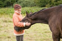 Frau pets Pferd. lizenzfreies stockbild