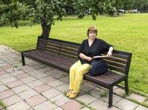 Frau plant, die Einbuchtung zu bearbeiten, die im Park in einer Mittagspause sitzt lizenzfreies stockfoto