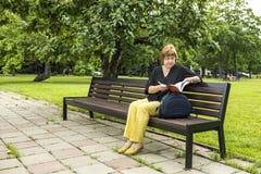 Frau plant, die Einbuchtung zu bearbeiten, die im Park in einer Mittagspause sitzt lizenzfreie stockfotografie