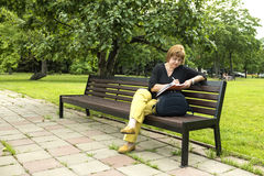 Frau plant, die Einbuchtung zu bearbeiten, die im Park in einer Mittagspause sitzt lizenzfreie stockfotos
