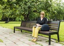 Frau plant, die Einbuchtung zu bearbeiten, die im Park in einer Mittagspause sitzt lizenzfreie stockbilder