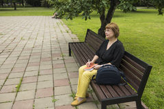 Frau plant, die Einbuchtung zu bearbeiten, die im Park in einer Mittagspause sitzt stockfoto