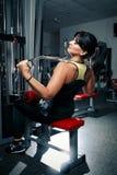 Frau plus Größe in der Turnhalle, die Übungen mit Trainingsapparaten tut, Stockbild