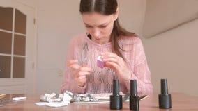 Frau poliert ihre Nägel mit Datei stock footage