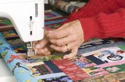 Frau quilter unter Verwendung des manuellen Gewindescherblockes Stockfotografie