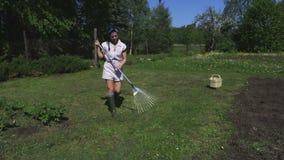 Frau räumt den Rasen auf stock video footage