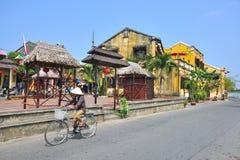 Frau reitet ein Fahrrad in Vietnam Stockfotografie