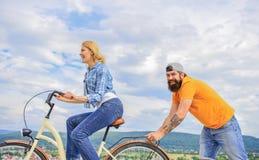 Frau reitet Fahrradhimmelhintergrund Stoß und Förderung Antrieb zum sich zu bewegen Mannstoßmädchen-Fahrfahrrad Stützhilfen stockfoto
