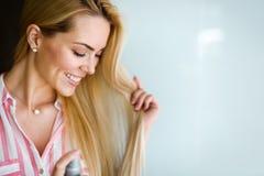 Frau repariert ihr Haar mit einem Haarspray lizenzfreies stockbild