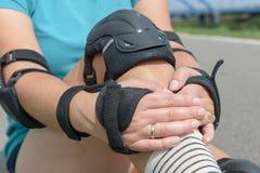 Frau Rollerskater, der auf Knieschutzauflagen auf ihrem Bein sich setzt stockbilder