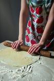 Frau Rolls-Teig-Nudelholz auf dem Küchentisch auf einem dunklen Hintergrund Strahln-Licht-Fälle auf dem Tisch in die Dunkelheit stockbilder
